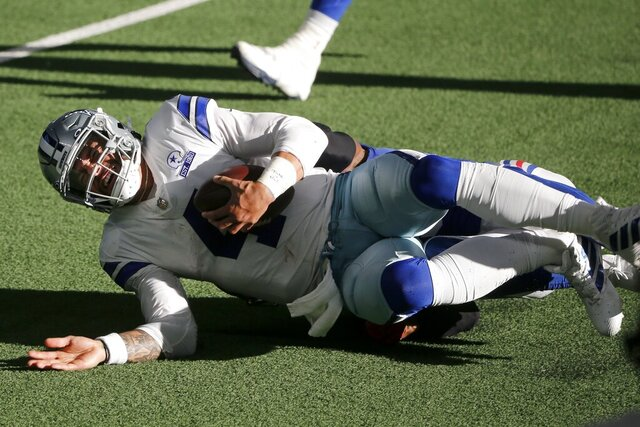 Dallas Cowboys quarterback Dak Prescott (4) is tackled by New York Giants cornerback Logan Ryan, rear, in the second half of an NFL football game in Arlington, Texas, Sunday, Oct. 11, 2020. Prescott suffered a lower right leg injury on the play. (AP Photo/Michael Ainsworth)