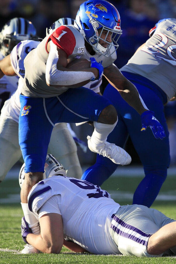 Kansas running back Pooka Williams Jr. (1) tries to step over Kansas State defensive tackle Jordan Mittie (91) during the second half of an NCAA college football game in Lawrence, Kan., Saturday, Nov. 2, 2019. Kansas State defeated Kansas 38-10. (AP Photo/Orlin Wagner)