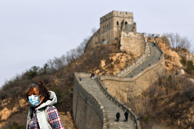 A woman wearing a protective face mask visits the Badaling Great Wall of China after it reopened for business following the new coronavirus outbreak in Beijing, China, Tuesday, March 24, 2020. Beijing's city zoo and parts of the Great Wall of China have reopened to visitors who book in advance, as the capital slowly returns to normal amid a sharp fall in the number of new coronavirus cases. (AP Photo/Andy Wong)