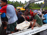 Rescuers sit beside a body bag containing the remains of a civilian victim when a Philippine military C-130 plane crashed in Patikul town, Sulu province, southern Philippines on Sunday July 4, 2021. A Philippine air force C-130 aircraft carrying combat troops assigned to fight Muslim militants crashed and exploded while landing in the south Sunday, killing dozens of army soldiers on board and three civilians on the ground in one of the worst disasters in the air force's history. (AP Photo/Nickee Butlangan)