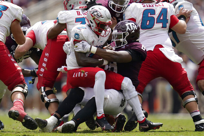 Texas A&M defensive lineman DeMarvin Leal (8) sacks New Mexico quarterback Terry Wilson (2) for a 7-yard loss during the second half of an NCAA college football game on Saturday, Sept. 18, 2021, in College Station, Texas. (AP Photo/Sam Craft)