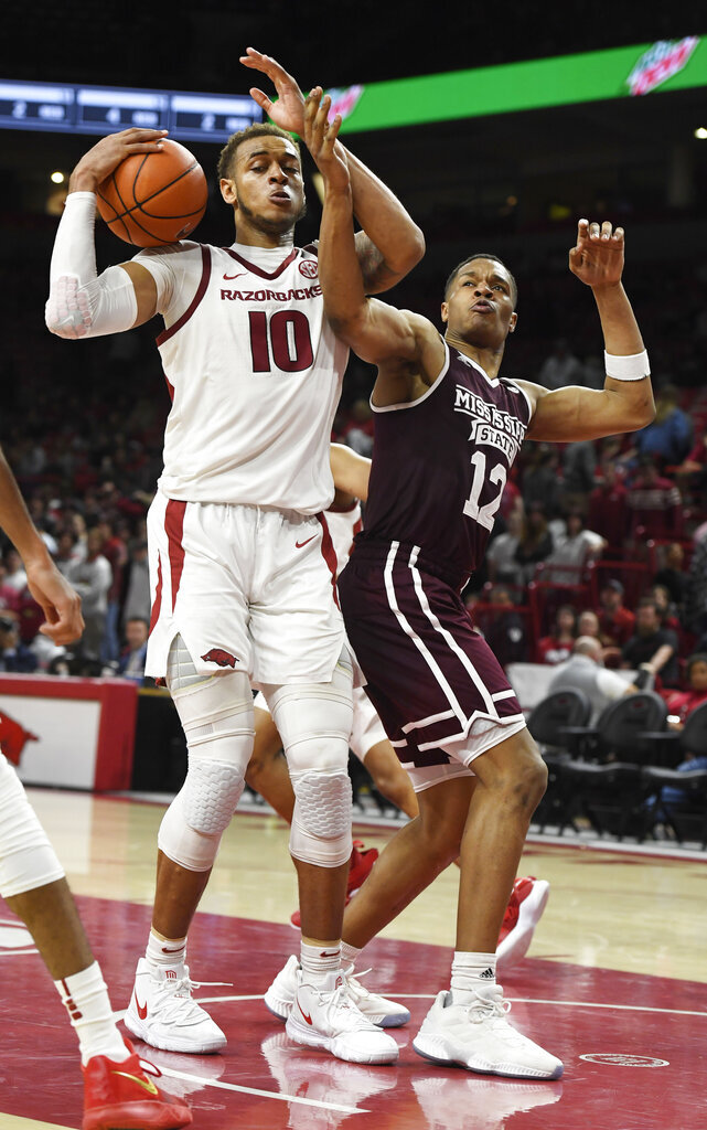 Mississippi State guard Robert Woodard II (12) and Arkansas forward Daniel Gafford (10) vie for a rebound during the second half of an NCAA college basketball game Saturday, Feb. 16, 2019, in Fayetteville, Ark. (AP Photo/Michael Woods)