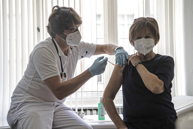 Patient Nicole Brusselaers, right, is vaccinated against the coronavirus with the Pfizer vaccine by family doctor Karl Schorn, left, in Berlin, Germany, Thursday, April 8, 2021. (Paul Zinken/dpa via AP)