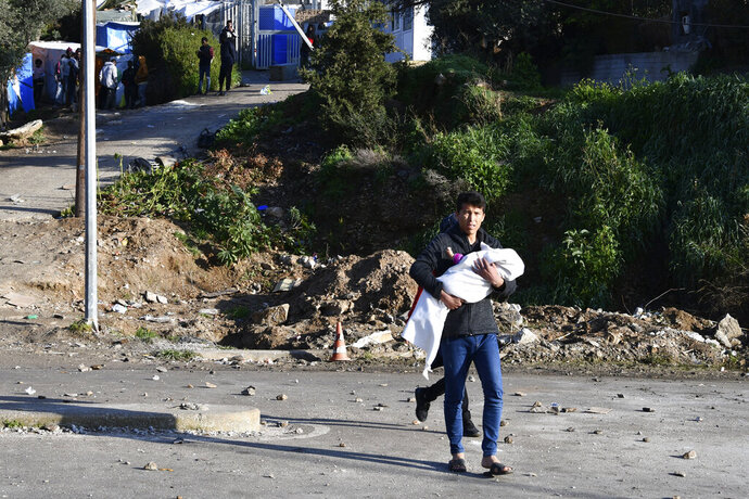 A man holds a baby as he walks outside a refugee camp after clashes on the eastern Greek island of Samos, Thursday, Dec. 19, 2019. Clashes broke out between police and a group of migrants at a refugee camp in Samos island, prompting the local mayor to shut down a nearby elementary school and kindergarten. (AP Photo/Michael Svarnias)
