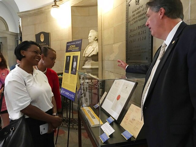 In this Sept. 7, 2019 photo, Kevin Cherry, deputy director of the North Carolina Department of Natural and Cultural Resources, guides visitors through an exhibit marking the 100th anniversary of the passage of the 19th Amendment, at the State Capitol in Raleigh, NC. The exhibit titled,