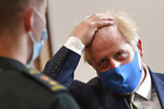 Britain's Prime Minister Boris Johnson, wearing a face mask, talks with a paramedic during a visit to the headquarters of the London Ambulance Service NHS Trust in London, Monday July 13, 2020. (Ben Stansall/Pool via AP)