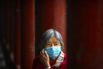 A woman wearing a face mask to protect against the coronavirus sits along a covered walkway at the Temple of Heaven in Beijing, Thursday, Oct. 1, 2020. Millions of Chinese tourists usually would use their week-long National Day holidays to travel abroad. This year, travel restrictions due to the coronavirus pandemic mean that some 600 million tourists - about 40% of the population - will travel within China during the holiday that began Thursday, according to Ctrip, China's largest online travel agency. (AP Photo/Mark Schiefelbein)