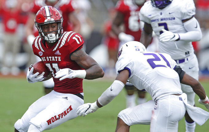 North Carolina State's Jakobi Meyers (11) runs the ball while James Madison's Adam Smith (21) looks for the tackle during the first half an NCAA college football game in Raleigh, N.C., Saturday, Sept. 1, 2018. (AP Photo/Gerry Broome)