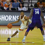 Texas guard Kerwin Roach II (12) drives around Kansas State forward Makol Mawien (14) during the first half of an NCAA college basketball game, Tuesday, Feb. 12, 2019, in Austin, Texas. (AP Photo/Michael Thomas)