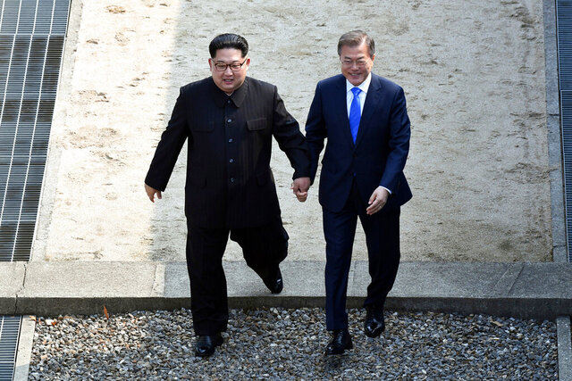 FILE - In this April 27, 2018, file photo, North Korean leader Kim Jong Un, left, and South Korean President Moon Jae-in cross the military demarcation line at the border village of Panmunjom in Demilitarized Zone. On both sides of the world's most heavily armed border Thursday, June 25, 2020, solemn ceremonies will mark the 70th anniversary of the outbreak of a war that killed and injured millions, left large parts of the Korean Peninsula in rubble and technically still continues. (Korea Summit Press Pool via AP. File)