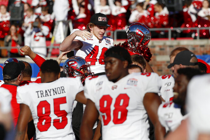 Western Kentucky placekicker Cory Munson, top center, is carried around the field on the shoulders of teammates after kicking the winning field goal in the First Responder Bowl NCAA college football game against Western Michigan in Dallas, Monday, Dec. 30, 2019. (AP Photo/Roger Steinman)
