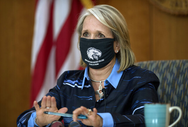 FILE - IN this Thursday, July 23, 2020 file photo, Gov. Michelle Lujan Grisham gives her weekly update on COVID-19 and the state's effort to contain it during a virtual news conference from the state Capitol in Santa Fe, N.M. Grisham was an early adopter of aggressive pandemic restrictions that included a mask mandate, self-quarantine orders for travelers and a ban on public gatherings -- now capped at five people. And the state previously joined federal pilot project on testing and contact tracing. (Eddie Moore/The Albuquerque Journal via AP)