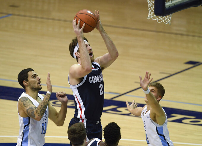 Gonzaga forward Drew Timme (2), center, shoots past San Diego forward Yavuz Gultekin (11), left, and guard Joey Calcaterra (2) during the first half of an NCAA college basketball game Thursday, Jan. 28, 2021, in San Diego. (AP Photo/Denis Poroy)