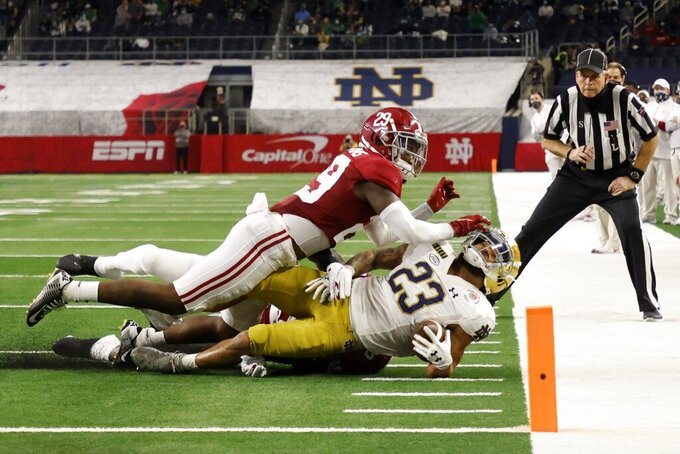 Notre Dame running back Kyren Williams (23) is tackled by Alabama defensive back DeMarcco Hellams (29) and others after a short gain in the first half of the Rose Bowl NCAA college football game in Arlington, Texas, Friday, Jan. 1, 2021. (AP Photo/Michael Ainsworth)