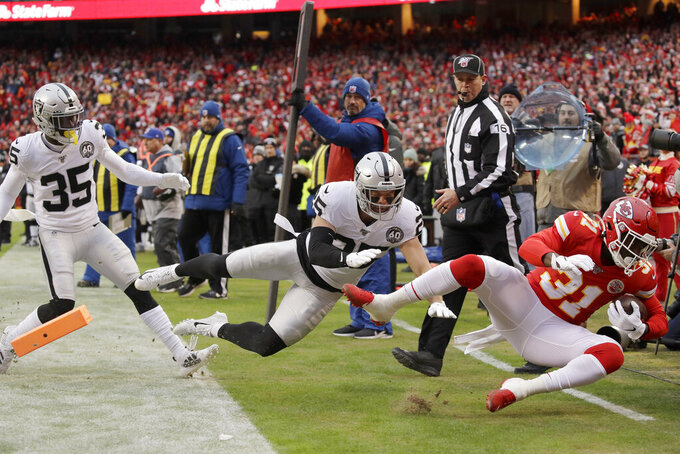 Kansas City Chiefs running back Darrel Williams (31) scores a touchdown against Oakland Raiders safety Erik Harris (25) and safety Curtis Riley (35), during the first half of an NFL football game in Kansas City, Mo., Sunday, Dec. 1, 2019. (AP Photo/Charlie Riedel)