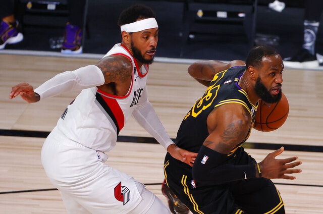 Los Angeles Lakers' LeBron James, right, drives against Portland Trail Blazers' Carmelo Anthony, left, during the second quarter of Game 4 of an NBA basketball first-round playoff series, Monday, Aug. 24, 2020, in Lake Buena Vista, Fla. (Kevin C. Cox/Pool Photo via AP)