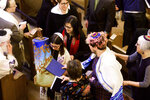 In this Saturday, Feb. 1, 2020, photo, Rabbi Jacqueline Mates-Muchin follows Hanna Raskin as she carries a Torah scroll during her bat mitzvah at Temple Sinai in Oakland, Calif. Mates-Muchin says there's extra worry as she feels obliged to be constantly mindful of her congregation's safety.  (AP Photo/Noah Berger)