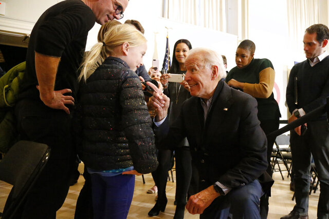 Democratic presidential candidate former Vice President Joe Biden kneels to greet Sydney Hansen, 9, of Oakland, Calif., during a campaign stop on Sunday, Dec. 29, 2019, in Peterborough, N.H. (AP Photo/Mary Schwalm)