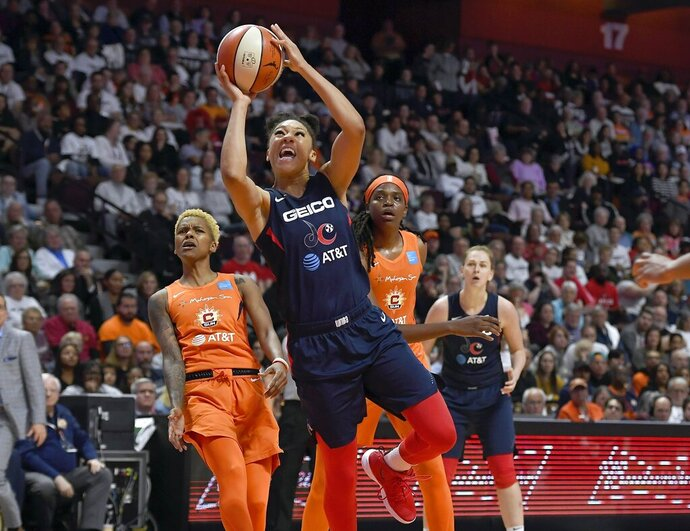 Washington Mystics' Aerial Powers, center, breaks past Connecticut Sun's Courtney Williams, left, and Jonquel Jones, right, for a layup during the second half in Game 3 of basketball's WNBA Finals, Sunday, Oct. 6, 2019, in Uncasville, Conn. (AP Photo/Jessica Hill)