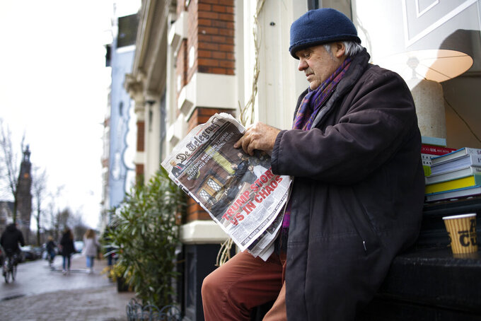"A man turns a page as he reads a newspaper with a headline reading ""Trump Plunges U.S. into Chaos"" outside a takeaway cafe in the center of Amsterdam, Netherlands, Thursday, Jan. 7, 2021. Congress confirmed Democrat Joe Biden as the presidential election winner early Thursday after a violent mob loyal to President Donald Trump stormed the U.S. Capitol in a stunning attempt to overturn America's presidential election, undercut the nation's democracy and keep Trump in the White House. (AP Photo/Peter Dejong)"