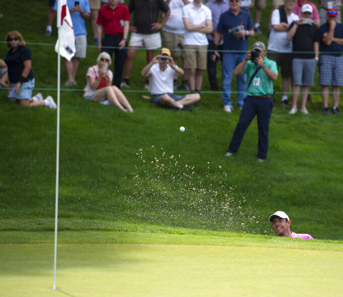 FILE - In this June 22, 2018, file photo, Rory McIlroy hits out of a bunker on the 18th hole during the second round of the Travelers Championship golf tournament at TPC River Highlands in Cromwell, Conn. The tournament director for this week's Travelers Championship thought about encircling the 18th green at TPC River Highlands with giant video boards that could be filled with images of fans watching the golf and cheering from home. Thursday's, June 25, 2020, tournament will be held without fans, but is still expected to raise significant funds for charity. (Patrick Raycraft/Hartford Courant via AP, File)