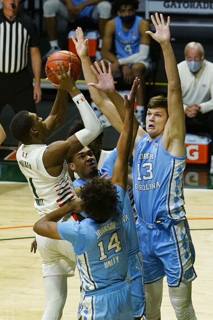 Miami forward Anthony Walker (1) jumps for a basket as North Carolina forward Walker Kessler (13) and guard Puff Johnson (14) defend during the first half of an NCAA college basketball game, Tuesday, Jan. 5, 2021, in Coral Gables, Fla.(AP Photo/Marta Lavandier)