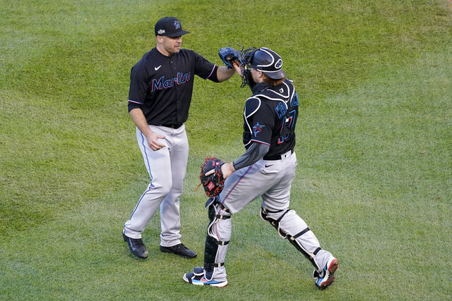 Miami Marlins relief pitcher Brandon Kintzler, left, and catcher Chad Wallach (17) celebrate a 2-0 victory over the Chicago Cubs in Game 2 of a National League wild-card baseball series Friday, Oct. 2, 2020, in Chicago. The Marlins won the series 2-0 to advance to the division series. (AP Photo/Nam Y. Huh)