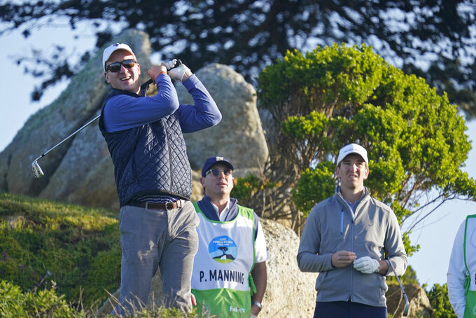FILE - In this Feb. 7, 2020, file photo, Peyton Manning, left, follows his shot from the 11th tee of the Monterey Peninsula Country Club Shore Course as his brother Eli Manning, right, stands nearby during the second round of the AT&T Pebble Beach National Pro-Am golf tournament in Pebble Beach, Calif. Peyton Manning plans to play a round of golf with an All In Challenge winner two guests, and then go to a restaurant for dinner with the winner and 10 guests. His recently retired brother, Eli, offered the Corvette he received as the MVP of the New York Giants' Super Bowl win over the Patriots in February 2012. (AP Photo/Tony Avelar, File)