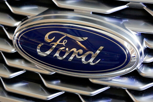 FILE- This Feb. 15, 2018, file photo shows a Ford logo on display at the Pittsburgh Auto Show. Ford is recalling more than 700,000 vehicles in North America because the backup cameras can show distorted images or suddenly go dark. The recall covers most 2020 versions of Ford's F-Series trucks, as well as the 2020 Explorer, Mustang, Transit, Expedition, Escape, Ranger and Edge.  The recall is expected to start Nov. 7, 2020.  (AP Photo/Gene J. Puskar, File)