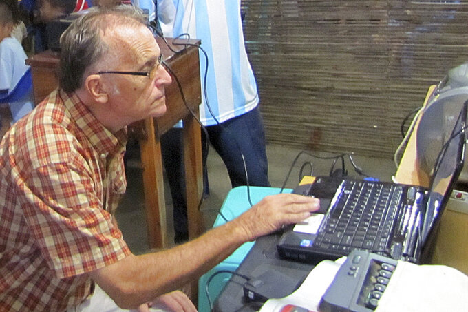 This 2010 photo provided to The Associated Press shows now-defrocked Catholic priest Richard Daschbach using a computer at the Topu Honis children's shelter in Kutet, East Timor. Daschbach is wanted in the U.S. for three counts of wire fraud linked to one of his California-based donors, which accused him in a court case of violating an agreement that he would protect those under his care. An Interpol Red Notice has been issued internationally for his arrest. (AP Photo)