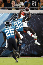 Cleveland Browns wide receiver Davion Davis, right, makes a catch for a touchdown over Jacksonville Jaguars cornerback Tyson Campbell (32) and defensive back Jarrod Wilson (25) during the first half of an NFL preseason football game, Saturday, Aug. 14, 2021, in Jacksonville, Fla. (AP Photo/Stephen B. Morton)