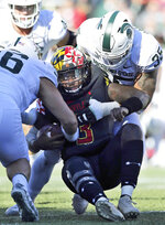 FILE - In this Saturday, Nov. 3, 2018, file photo, Maryland quarterback Tyrrell Pigrome, center, is tackled by Michigan State's Joe Bachie, right, in the second half of a NCAA college football game in College Park, Md. Bachie, who is from Brook Park, Ohio, was named the Big Ten defensive player of the week after he forced a career-high three fumbles, matched a career-high two pass breakups and had seven tackles in a 24-3 win at Maryland. (AP Photo/Gary Cameron, File)