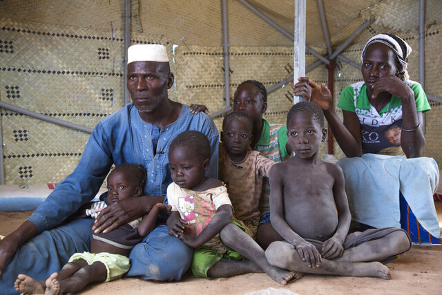 In this photograph taken Wednesday Nov. 13, 2019 and released by the World Food Program (WFP), Zore Yusef, 61, and his family, sit in the Pissila camp, north of the capital Ouagadougou, Burkina Faso. Yusef was displaced from the Sahel region due to armed conflict in northern Burkina. The U.N. on Tuesday said a humanitarian crisis is growing in West Africa's arid Sahel region where insecurity linked to growing extremist attacks has forced more than 860,000 people in Burkina Faso, Mali and Niger to flee their homes. (Marwa Awad/WFP via AP)