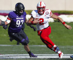 Nebraska's Adrian Martinez, right, runs upfield past Northwestern's Joe Gaziano during the first half of an NCAA college football game Saturday, Oct. 13, 2018, in Evanston, Ill.. (AP Photo/Jim Young)