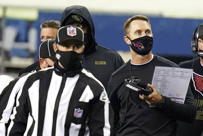 Arizona Cardinals head coach Kliff Kingsbury, right, looks toward the scoreboard during the second half of an NFL football game against the Seattle Seahawks, Thursday, Nov. 19, 2020, in Seattle. (AP Photo/Elaine Thompson)
