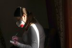 Dr. Viktoria Mahnych, wearing face mask against coronavirus, writes down a note as she visits a patient with COVID-19 in Verhovyna village, Ivano-Frankivsk region of Western Ukraine, Wednesday, Jan. 6, 2021. Mahnych fears that a lockdown in Ukraine came too late and the long holidays, during which Ukrainians frequented entertainment venues, attended festive parties and crowded church services, will trigger a surge in new coronavirus infections. (AP Photo/Evgeniy Maloletka)