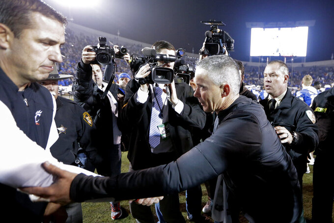 Memphis head coach Mike Norvell, right, shake hands with Cincinnati head coach Luke Fickell, left, after the NCAA college football game for the American Athletic Conference championship Saturday, Dec. 7, 2019, in Memphis, Tenn. (AP Photo/Mark Humphrey)