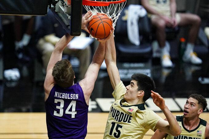Purdue center Zach Edey (15) blocks the shot of Northwestern center Matthew Nicholson (34) during the first half of an NCAA college basketball game in West Lafayette, Ind., Saturday, Feb. 6, 2021. (AP Photo/Michael Conroy)