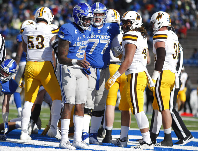 Air Force quarterback Donald Hammond III, front, celebrates his one-yard-touchdown run as offensive lineman Parker Ferguson, back, comes in to congratulate him in the first half of an NCAA college football game against Wyoming, Saturday, Nov. 30, 2019, at Air Force Academy, Colo. (AP Photo/David Zalubowski)