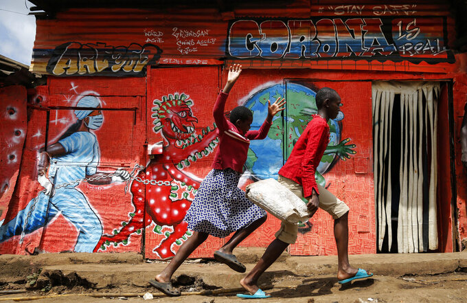 FILE - In this June 3, 2020, file photo, children run down a street past an informational mural warning people about the dangers of coronavirus in the Kibera slum of Nairobi, Kenya. Africa has surpassed 100,000 confirmed deaths from COVID-19 as the continent praised for its early response to the pandemic now struggles with a dangerous resurgence and medical oxygen often runs desperately short. (AP Photo/Brian Inganga, File)