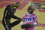 Racing Point driver Sergio Perez of Mexico, right, celebrates his first place with second place Renault driver Esteban Ocon of France in the Formula One Bahrain Grand Prix in Sakhir, Bahrain, Sunday, Dec. 6, 2020. (Tolga Bozoglu, Pool via AP)