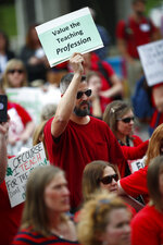 Kevin Johnson, a teacher in Denver Public Schools, holds up a placard during a rally outside the State Capitol, Monday, April 16, 2018, in Denver. Teachers from around the state were on hand to demand better salaries as lawmakers under the dome were set to debate a pension reform measure to cut retirement benefits as well as take-home pay. (AP Photo/David Zalubowski)