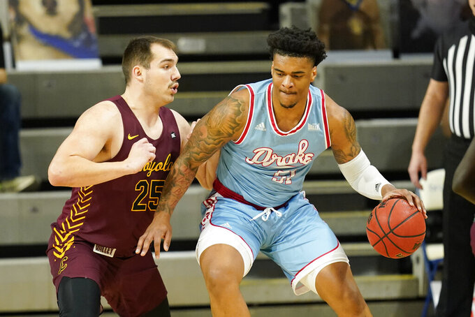 Drake forward Darnell Brodie drives around Loyola of Chicago center Cameron Krutwig, left, during the first half of an NCAA college basketball game, Saturday, Feb. 13, 2021, in Des Moines, Iowa. (AP Photo/Charlie Neibergall)