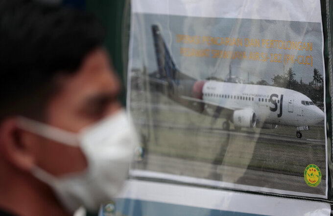 FILE - In this in this Jan. 10, 2021, file photo, a man walks past a picture of a Sriwijaya Air passenger jet that crashed off Java island, put up at the command center for the search and rescue mission at Tanjung Priok Port in Jakarta, Indonesia. A malfunctioning automatic throttle may have caused the pilots of the Sriwijaya Air jet to lose control, leading to the plane's plunge into the Java Sea last month, Indonesian investigators said Wednesday, Feb. 10, 2021. (AP Photo/Dita Alangkara, File)