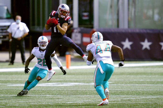 New England Patriots wide receiver Julian Edelman (11) catches a pass between Miami Dolphins safety Bobby McCain (28) and linebacker Elandon Roberts (44) in the first half of an NFL football game, Sunday, Sept. 13, 2020, in Foxborough, Mass. (AP Photo/Charles Krupa)