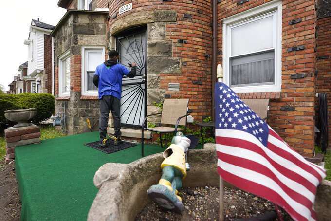 Sirgregory Allen leaves a flyer at a home in Detroit, Tuesday, May 4, 2021. Officials are walking door-to-door to encourage residents of the majority Black city to get vaccinated against COVID-19 as the city's immunization rate lags well behind the rest of Michigan and the United States. (AP Photo/Paul Sancya)