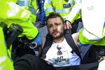 Police arrest protesters as they block traffic on London's Oxford Circus, Thursday, April 18, 2019. The group Extinction Rebellion is calling for a week of civil disobedience against what it says is the failure to tackle the causes of climate change. (AP Photo/Vudi Xhymshiti)