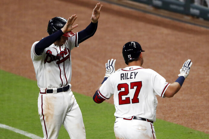 Atlanta Braves' Austin Riley (27) celebrates with teammate Freddie Freeman without contact after hitting a three-run home run in the fifth inning of a baseball game against the Toronto Blue JaysTuesday, Aug. 4, 2020, in Atlanta. (AP Photo/John Bazemore)