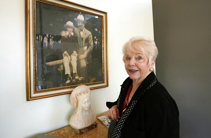 """Diane Capone discusses her family near a photograph of her father, Albert """"Sonny"""" Capone, as a young boy and her grandfather Al Capone on display at Witherell's Auction House in Sacramento, Calif., Wednesday, Aug. 25, 2021. The granddaughter of the famous mob boss and her two surviving sisters will sell 174 family heirlooms at an Oct. 8 auction titled """"A Century of Notoriety: The Estate of Al Capone, that will be held by Witherell's in Sacramento. (AP Photo/Rich Pedroncelli)"""