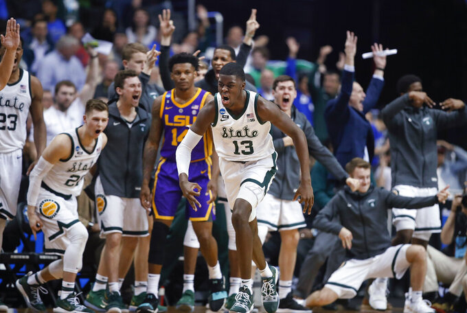 Michigan State forward Gabe Brown (13) and teammates react after he scored against LSU guard Marlon Taylor (14) during the second half of a semifinal in the NCAA men's college basketball tournament East Region in Washington, Friday, March 29, 2019. (AP Photo/Alex Brandon)